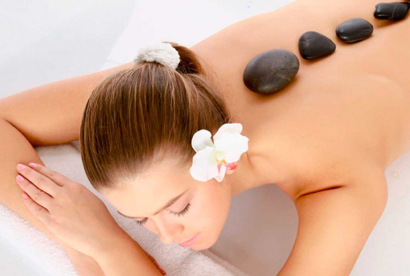 How is a hot stone massage performed?